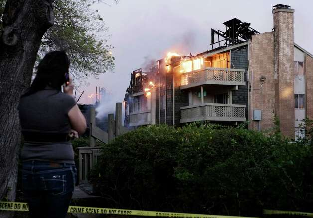 A spectator watches apartment buildings burn, Monday, Feb. 25, 2013, in the 10300 block of Sahara St. in San Antonio. Photo: Darren Abate, Darren Abate/For The Express-New