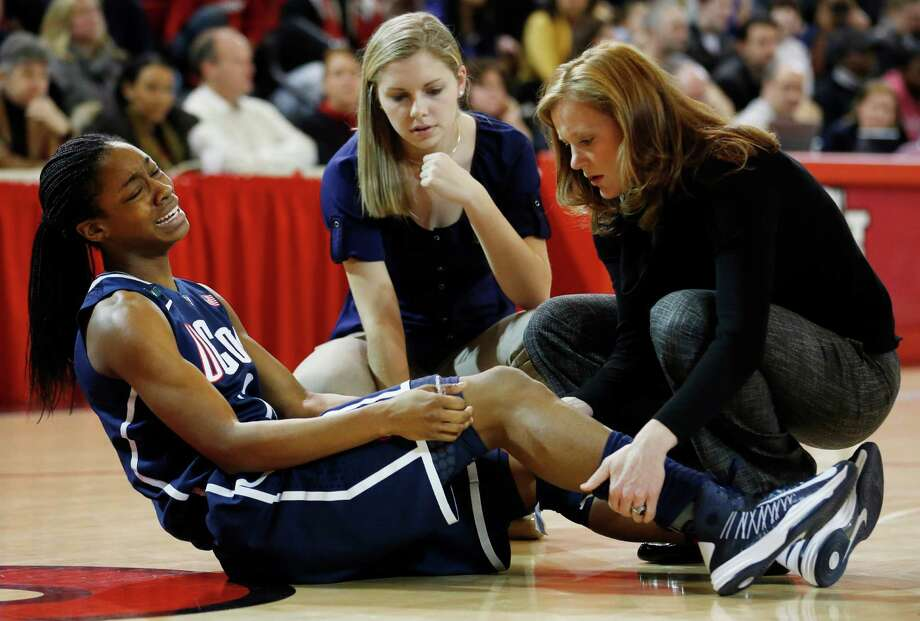 Connecticut guard Brianna Banks (13) winces in pain after an injury during the first half of a NCAA college basketball game against St. John's, Saturday, Feb. 2, 2013, at St. John's University in New York. (AP Photo/John Minchillo) Photo: John Minchillo, Associated Press / FR170537 AP