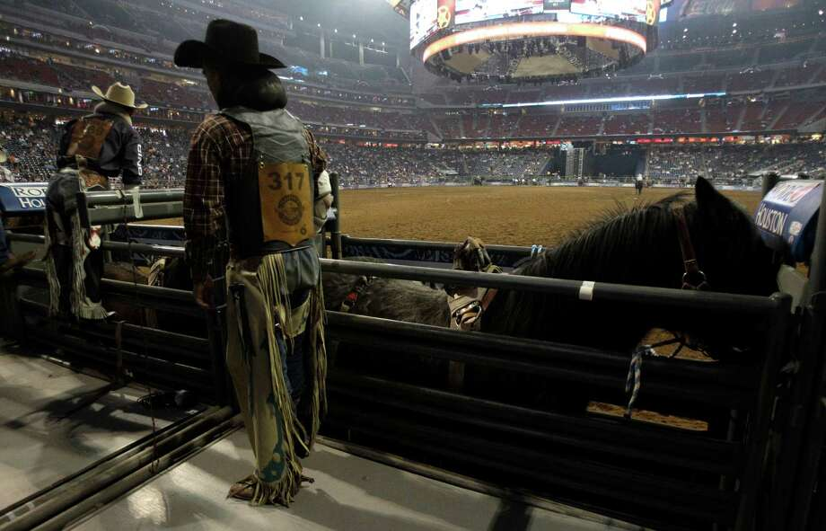 Bareback riders Will Lowe, left, and Tyler Scales, right,  prepare for their event during RodeoHouston at the Houston Livestock Show and Rodeo at Reliant Stadium Monday, Feb. 25, 2013, in Houston. Photo: Melissa Phillip, Houston Chronicle / © 2013  Houston Chronicle