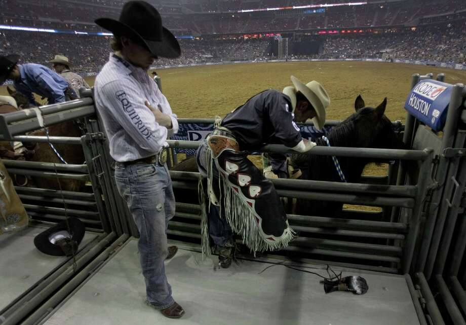 Bareback rider Will Lowe, right, prepares to ride Hi Roller during RodeoHouston at the Houston Livestock Show and Rodeo at Reliant Stadium Monday, Feb. 25, 2013, in Houston. Photo: Melissa Phillip, Houston Chronicle / © 2013  Houston Chronicle