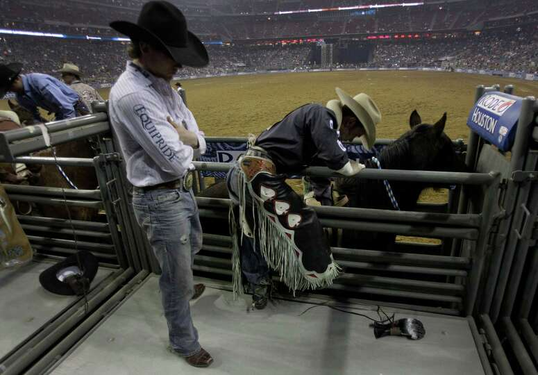 Bareback rider Will Lowe, right, prepares to ride Hi Roller during RodeoHouston at the Houston Lives