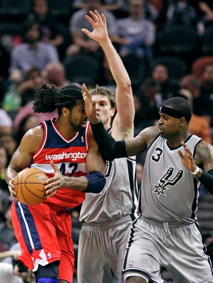 Washington Wizards' Nene looks for room around the Spurs' Tiago Splitter and Stephen Jackson during first half action Saturday, Feb. 2, 2013 at the AT&T Center. Photo: Edward A. Ornelas, San Antonio Express-News / © 2013 San Antonio Express-News