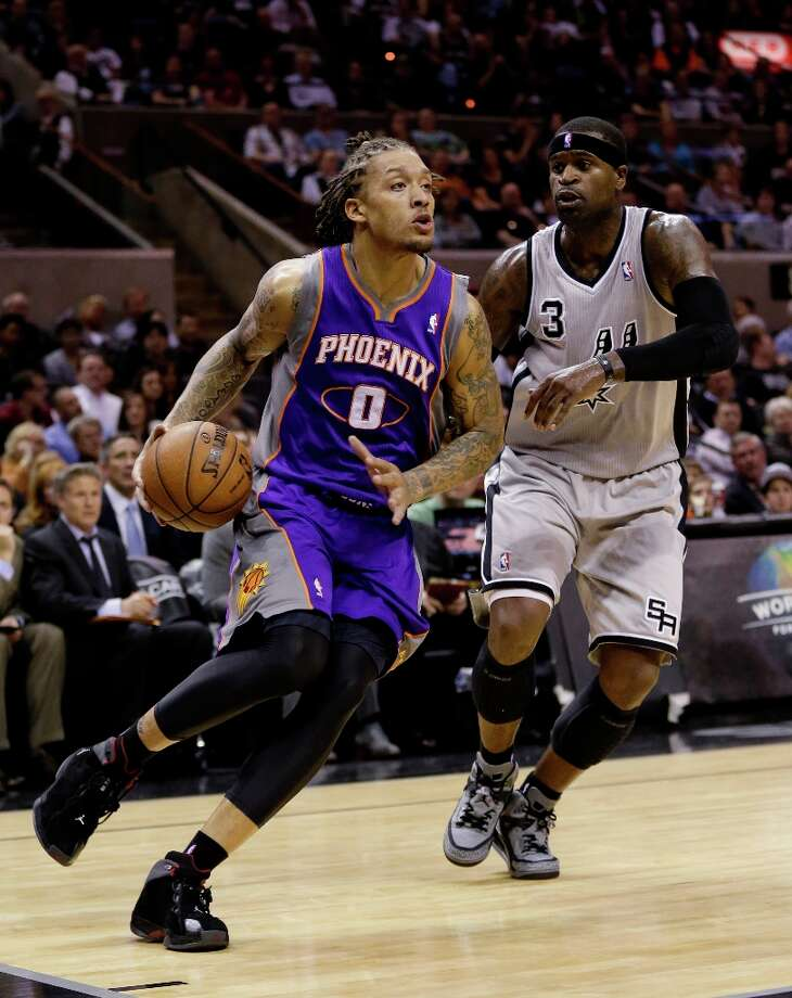 Phoenix Suns' Michael Beasley (0) drives around the Spurs' Stephen Jackson (3) during the fourth quarter Saturday, Jan. 26, 2013, in San Antonio. San Antonio won 108-99. Photo: Eric Gay, Associated Press / AP