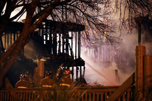 Firefighters work the scene of a fire at the Wood Hollow Apartment Homes in the 10,300 block of Sahara Drive Monday Feb. 25, 2013. Photo: Edward A. Ornelas, San Antonio Express-News / © 2013 San Antonio Express-News
