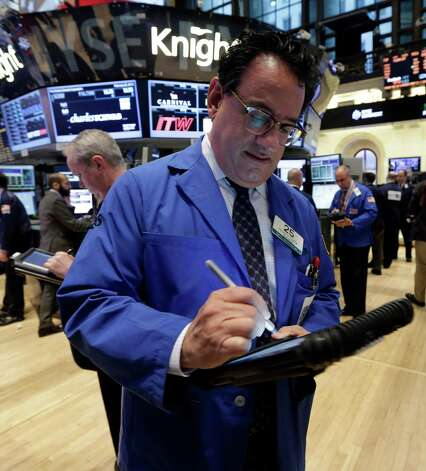 Trader Peter Costa, center, works on the floor of the New York Stock Exchange Monday, Feb. 25, 2013. Stocks are opening higher on Wall Street, following the first weekly decline in the S&P 500 index this year. (AP Photo/Richard Drew) Photo: Richard Drew