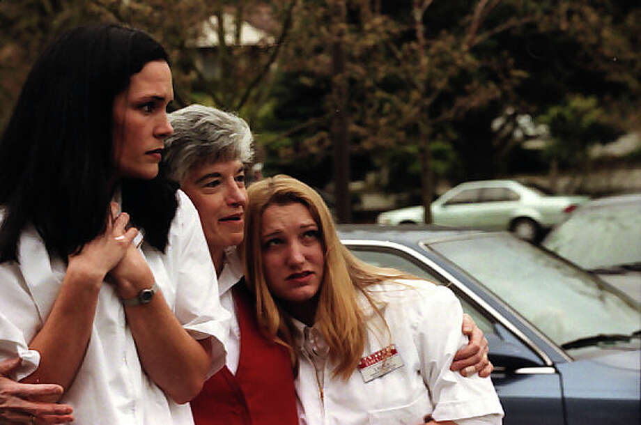 P-I photographer Phil H. Webber was near the Magnolia Bartell Drugs when the 2001 Nisqually earthquake hit. He captured this image of frightened workers afterward. This frame was not previously published. Notes with the archived negatives does not list thier names, but the newspaper identified them as Emily Purcell, Roseann Stella  and Laura Wray. Photo: Phil H. Webber/MOHAI Seattle Post-Intelligencer Collection/seattlepi.com File