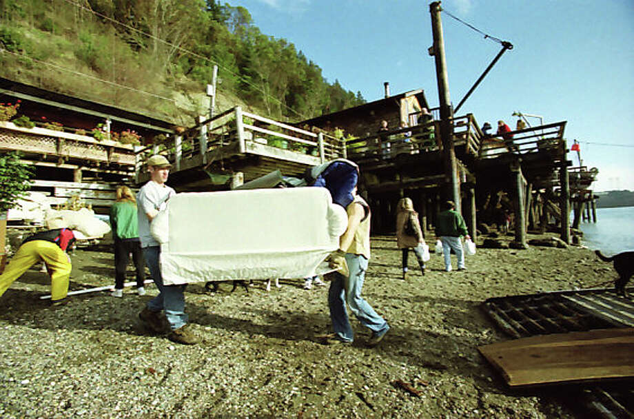 Residents of Tacoma's historic Salmon Beach neighborhood evacuate with their belongings onto a boat after earthquake triggered landslides destroyed several waterfront houses. This specific frame from Feb. 28, 2001 was not previously published. Photo: Paul Joseph Brown/MOHAI Seattle Post-Intelligencer Collection/seattlepi.com File
