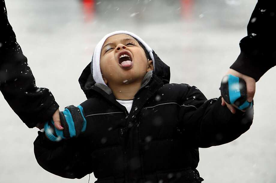 Roberto Alvarez, 3, tried to catch snowflakes as he walks into Festival Foods with his mother, Bianca Peregrina, right, and cousin, Paul Rocha, in Kansas City, Missouri, Monday, February 25, 2013.  Photo: Keith Myers, McClatchy-Tribune News Service