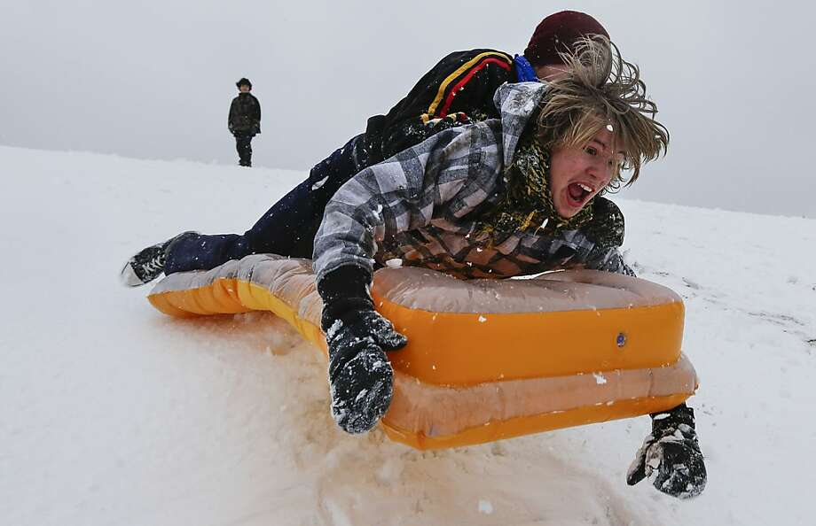 Simon Mourning, front, and Chance Cain fly into the air as they sled down a hill near downtown Wichita, Kansas on Monday, February 25, 2013.  Photo: Travis Heying, McClatchy-Tribune News Service