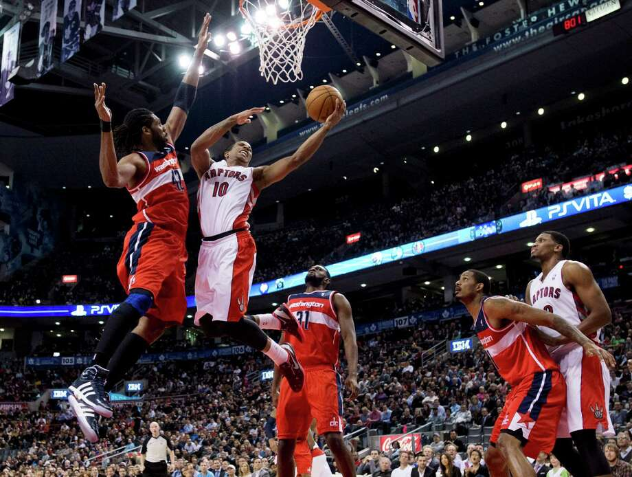 Toronto Raptors guard DeMar DeRozan (10) drives to the basket against Washington Wizards center Nene (42) as Wizards forwards Chris Singleton (31) and Trevor Ariza (1) watch while boxing out Raptors forward Rudy Gay, right, during the first half of their NBA basketball game, Monday, Feb. 25, 2013, in Toronto. (AP Photo/The Canadian Press, Frank Gunn) Photo: Frank Gunn