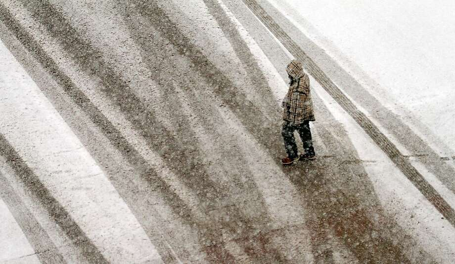 A pedestrian make his way through heavy snowfall in downtown Wichita, Kan., Monday, Feb. 25, 2013.  Photo: Mike Hutmacher, Associated Press