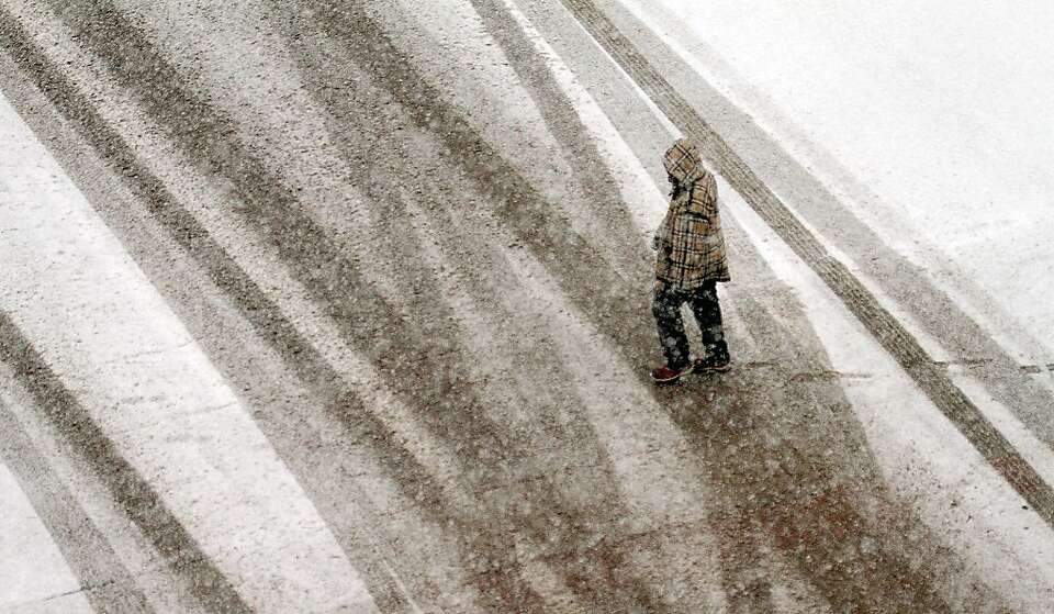 A pedestrian make his way through heavy snowfall in downtown Wichita, Kan., Monday, Feb. 25, 2013.