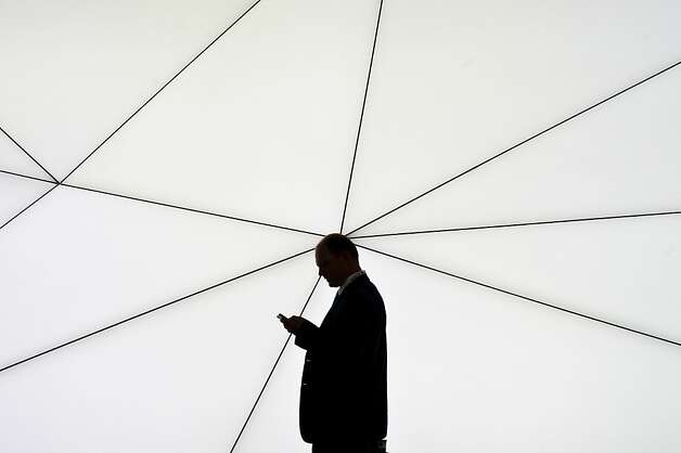 A visitor checks his mobile phone as he walks past a Samsung stand during the first day of the Mobile World Congress 2013 at the Fira Gran Via complex on February 25, 2013 in Barcelona, Spain. The annual Mobile World Congress hosts some of the world's largest communication companies, with many unveiling their latest phones and gadgets. The show runs from February 25 - February 28.  Photo: David Ramos, Getty Images