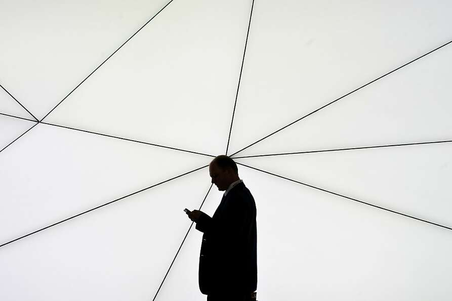 A visitor checks his mobile phone as he walks past a Samsung stand during the first day of the Mobil