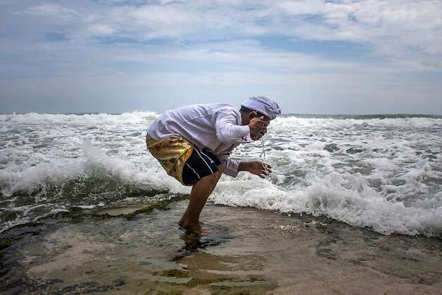 A Hindu priest washes his face with sea water during a religious ceremony called Melasti on Ngobaran Beach in Yogyakarta, Indonesia, Monday, Feb. 25, 2013. Melasti is performed a week ahead of Balinese Hindu's Day of Silence to purify the universe from bad influences, bad deeds and bad thoughts.  Photo: Gembong Nusantara, Associated Press