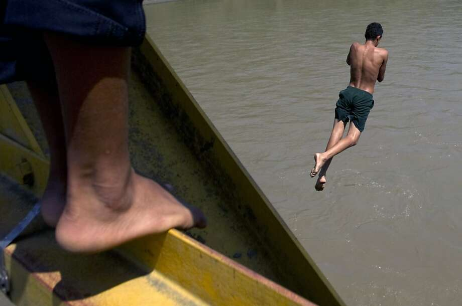 A man jumps into the Cauca river in Bolombolo municipality, south of Medellin, Antioquia department, Colombia on February 25, 2013. Tourists pay one dollar to men who jump.  Photo: Raul Arboleda, AFP/Getty Images