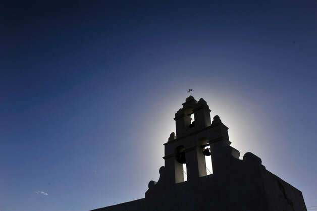 Late afternoon sun outlines the bell tower of Mission San Juan Capistrano. The exterior of the mission was covered in lime plaster.