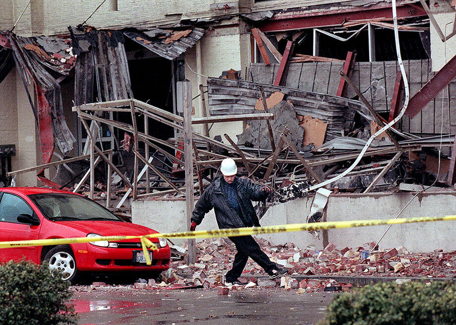 This was one of the published P-I photos taken after the 2001 Nisqually Earthquake, and the original caption read: A tow truck driver kicks bricks to the side from the earthquake damaged Sodo building in Seattle before towing away a car that was damaged there during Wednesday's quake which measured 6.8 on the richter scale. Photo: Renee C. Byer/seattlepi.com File, SEATTLE POST INTELLIGENCER  / -