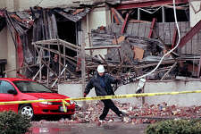 This was one of the published P-I photos taken after the 2001 Nisqually Earthquake, and the original caption read: A tow truck driver kicks bricks to the side from the earthquake damaged Sodo building in Seattle before towing away a car that was damaged there during Wednesday's quake which measured 6.8 on the richter scale.