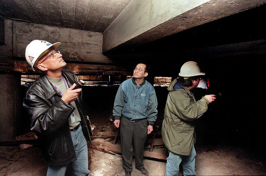 This was one of the published P-I photos taken after the 2001 Nisqually Earthquake, and the original caption for this March 1 photo read: Kaveh Aminian check for cracks in the foundation of the Dong Vinh Restaurant Equipment warehouse in the Sodo disrtict. Aminian (L) and fellow inspector Will McDonald (R) are with the King County Dept. of Construction and Land Use and are inspecting build damaged in Wednesday's earthquake. In the center is Danny Hong. Photo: Gilbert Arias/seattlepi.com File, SEATTLE POST INTELLIGENCER  / -
