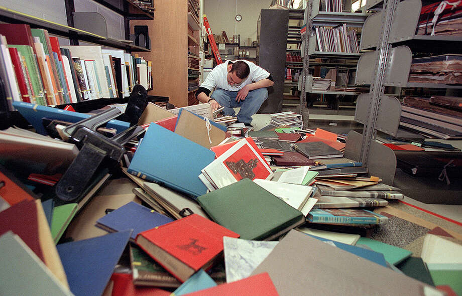 This was one of the published P-I photos taken after the 2001 Nisqually Earthquake, and the original caption for this March 1 picture read: At the Seattle City Library, Jon Tulchin helps other staffers clean up the mounds of books that fell during the earthquake. The Central Library is tentatively set to close on June 9, 2001 and reopen at it's temporary location at 800 Pike St. until a the new build is construted on the existing site. Photo: Gilbert Arias/seattlepi.com File, SEATTLE POST INTELLIGENCER  / -