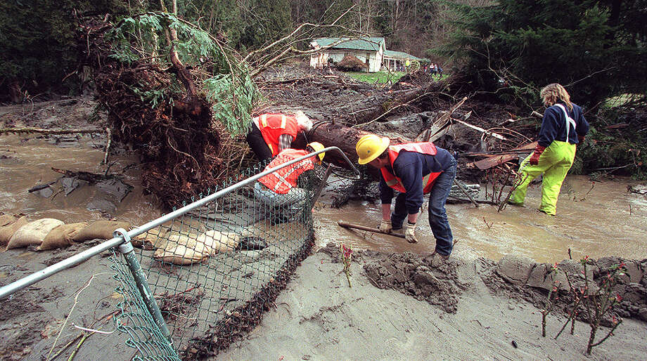 This was one of the published P-I photos taken after the 2001 Nisqually Earthquake, and the original caption for the March 2 photo read: A King County Road Crew work on diverting a small stream so it no longer flows into Reva Chareoneau's home on Southeast Jones Place in Renton. Wednesday's earthquake shook loose a land slide that stopped just four feet from Chareoneau's home but destroyed the white house in the back ground owned by Paula and Robert VanDorssen (14804 S.E. Jones Pl.). Photo: Grant M. Haller/seattlepi.com File / -