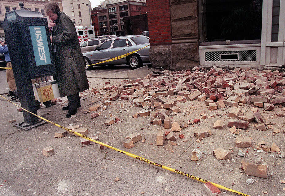This was one of the published P-I photos taken after the 2001 Nisqually Earthquake, and the original caption read: A man crosses the police line to make a phone call on 2nd Avenue South in the Pioneer Square district of Seattle where bricks fell down near the Cafe Hue after the earthquake. Photo: Renee C. Byer/seattlepi.com File, SEATTLE POST INTELLIGENCER  / -