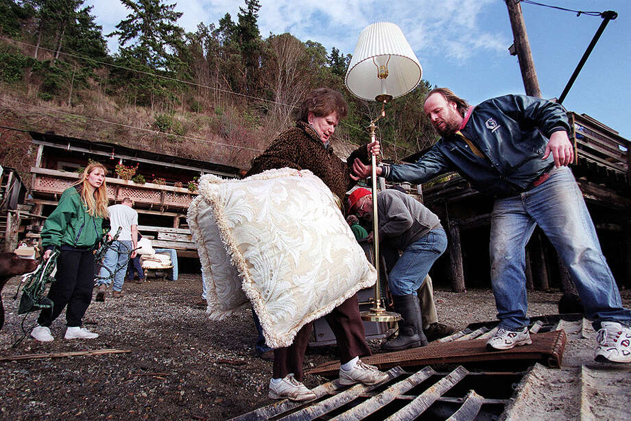 This was one of the published P-I photos taken after the 2001 Nisqually Earthquake, and the original caption read: Residents of Tacoma's historic Salmon Beach neighborhood evacuate with their belongings onto a boat after earthquake triggered landslides destroyed several waterfront houses. Photo: Paul Joseph Brown/seattlepi.com File / -