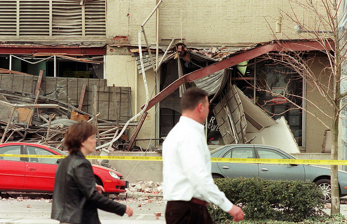 People walk past the Starbucks building on 1st Ave South and survey the earthquake damage.