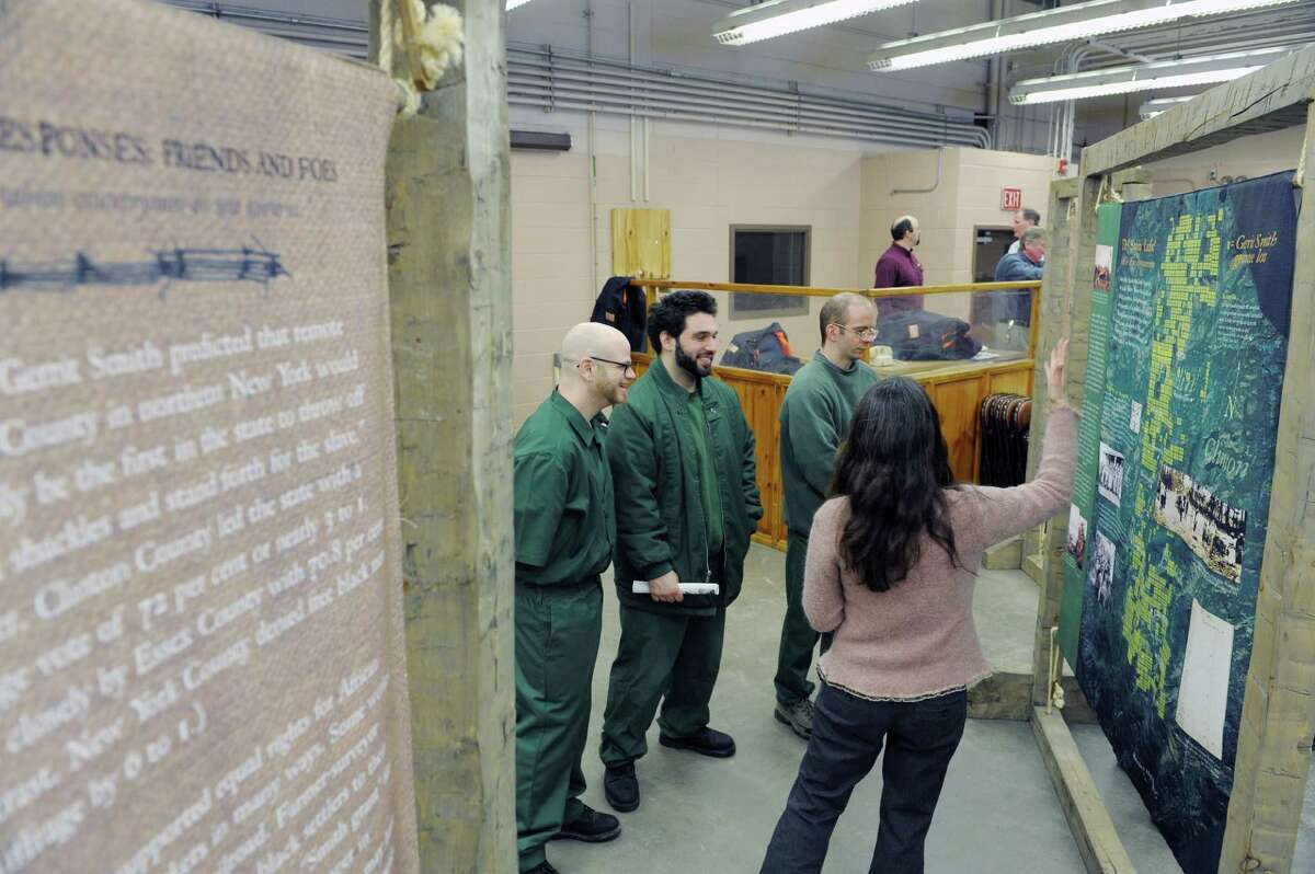 Suzanne Orlando, foreground, librarian at the Adirondack Correctional Facility, talks with inmates from left to right, Charles Young, Geoffrey Goldman and Matthew Card about the exhibit