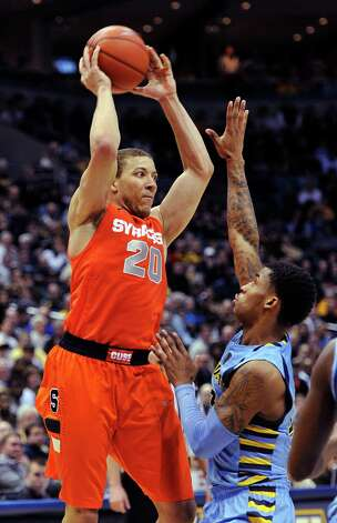 Syracuse's Brandon Triche (20) looks to pass over Marquette's Vander Blue during the second half of an NCAA college basketball game, Monday, Feb. 25, 2013, in Milwaukee. (AP Photo/Jim Prisching) Photo: Jim Prisching
