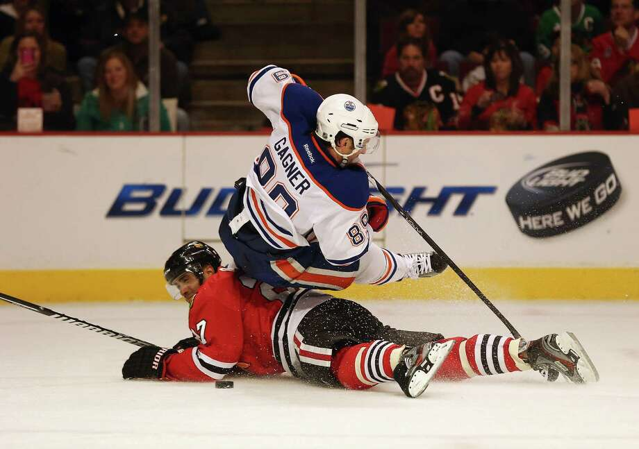 Johnny Oduya of the Blackhawks, left, upends the Oilers' Sam Gagner at Chicago's United Center. Photo: Jonathan Daniel, Staff / 2013 Getty Images