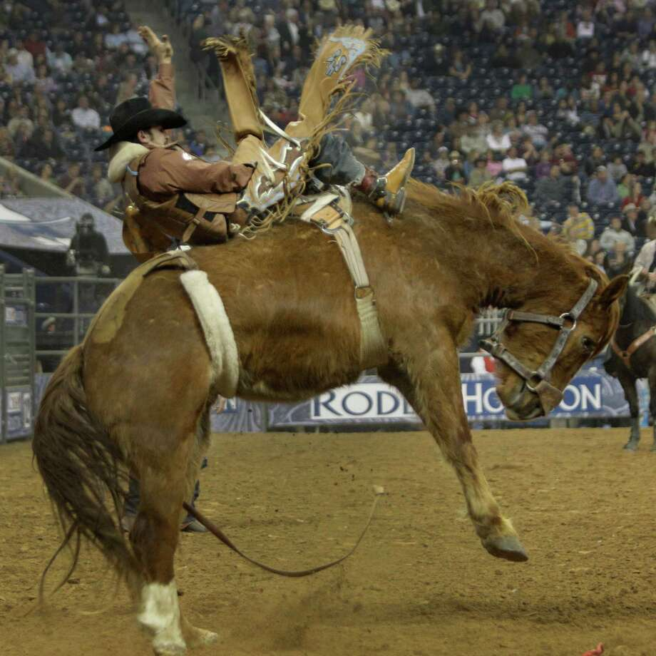 RodeoHouston got under way at Reliant Stadium on Monday night, with Richmond Champion of The Woodlands getting sideways during his Super Series I bareback ride and Winn Ratliff of Leesville, La., grabbing the first-round lead with a score of 85.5. Champion is seventh at 69.5. Second-round competition in all events is Tuesday. Photo: Melissa Phillip, Staff / © 2013  Houston Chronicle