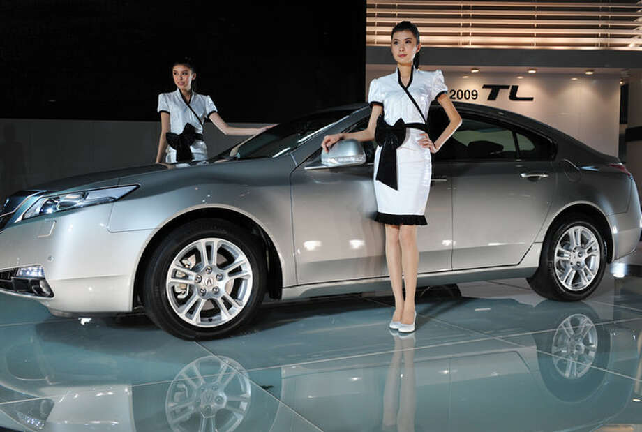 Two models stand next to a Honda 2009 Acura TL car at the Auto Guangzhou 2008 Exhibition in Guangzhou of Guangdong Province.