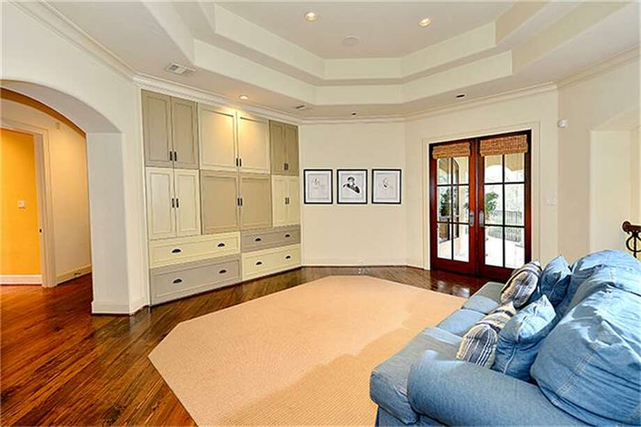 Upstairs game room has built ins for TV and toys, and opens to balcony. Photo: Better Homes And Gardens Real Estate Gary Greene