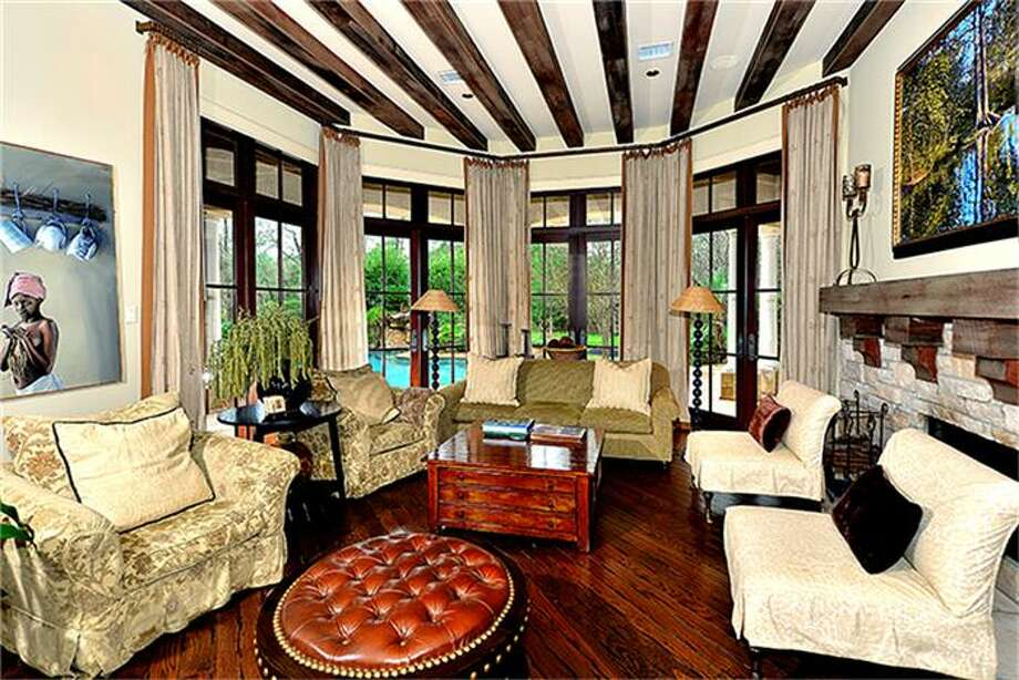 Sophisticated and spacious, family room with fireplace holds cozy charm. Doors grant convenient access to outdoor living spaces. Photo: Better Homes And Gardens Real Estate Gary Greene