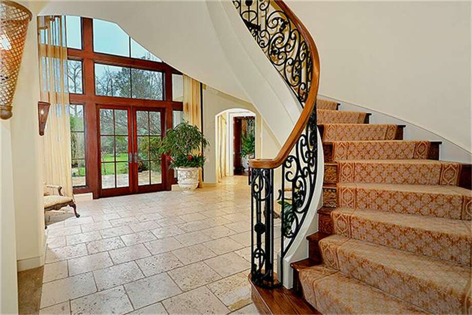 Sweeping iron staircase with atrium in background. More doors and windows welcome the outdoors in. Photo: Better Homes And Gardens Real Estate Gary Greene