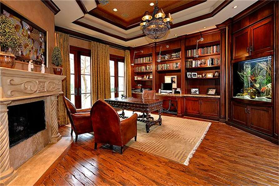 Just off entryway, richly appointed office has fireplace and built-ins which include custom aquarium