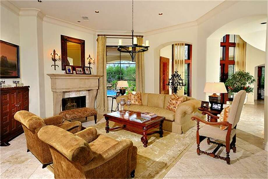 Living room, with fireplace, is also framed with archways, keeping an open feeling and nice flow for entertaining. Photo: Better Homes And Gardens Real Estate Gary Greene