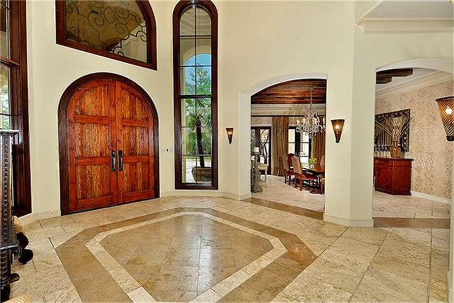 Foyer view of front entrance's majestic custom doors. Graceful arches frame the formal dining room. Photo: Better Homes And Gardens Real Estate Gary Greene