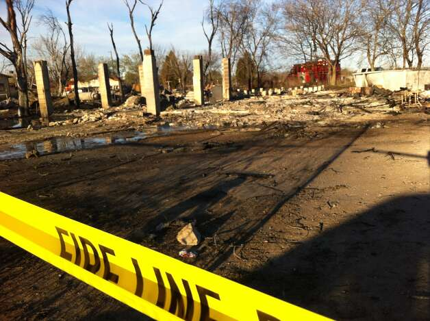 Fire crews investigate the site of a wind-fueled fire that killed three people Monday afternoon. Photo: Ana Ley/Express-News