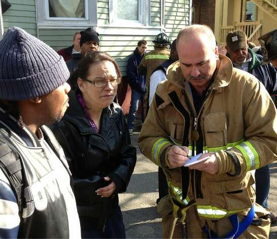 An Albany firefighter interviews the occupant of a building on fire at 268 Sheridan Ave. on Tuesday, Feb. 26, 201. (Skip Dickstein/Times Union)