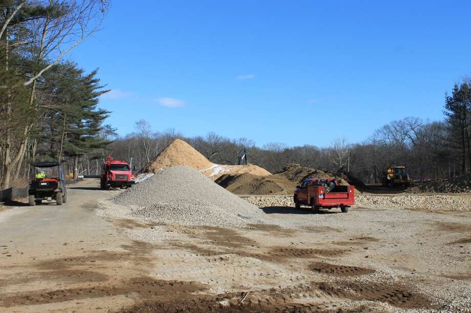 Looking eastward down Sunny Lane (aka Allen Raymond Lane). The new Y facility will be situated to the right of the tall pile of wood chips. The Merritt Parkway, to the left, runs parallel to the lane. The red service truck is on what will be the new parking lot.