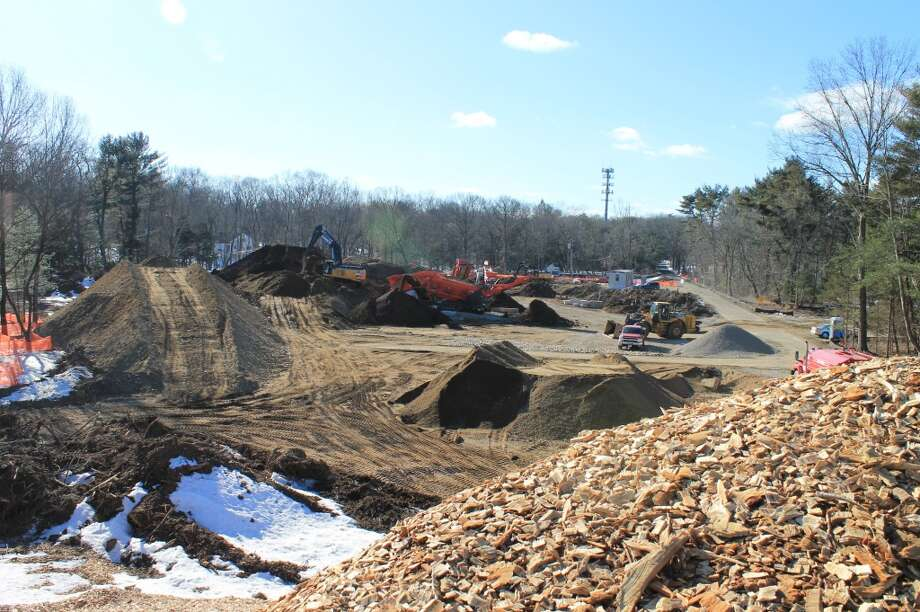 An overview of the building site, looking west from the top of a tall mound of wood chips. Heavy-duty equipment is screening topsoil and gravel on what will be the new Y's parking lot.