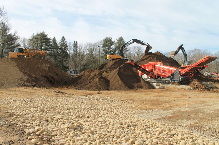 Equipment piling topsoil and excavated material, which will be processed and re-used on-site.