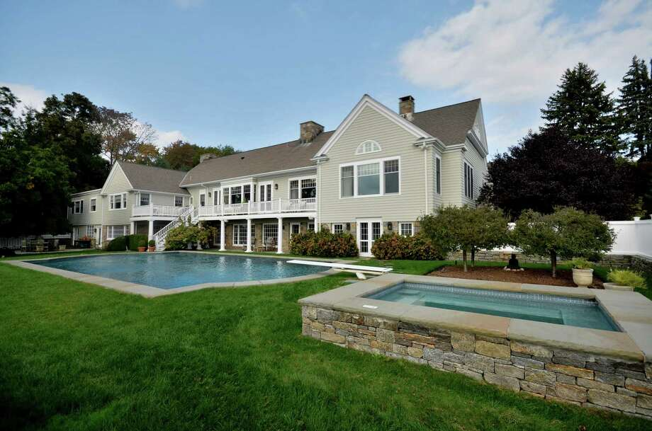 This stone and shingle house, designed by Louise Brooks, at 994 Oenoke Ridge Road in New Canaan, sits on almost five professionally landscaped acres, complete with stone walls, terraces, an oversized pool and spa. Photo: Contributed