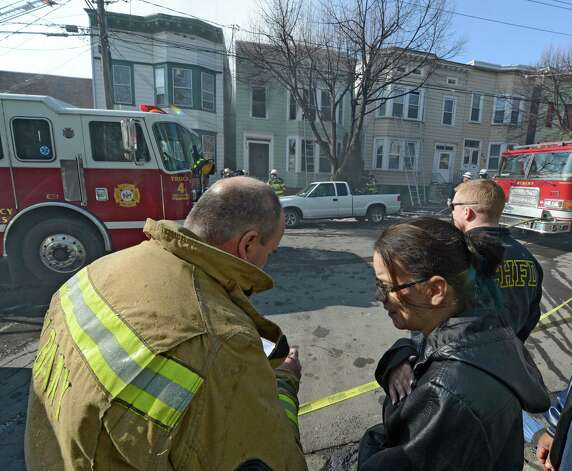 An Albany firefighter interviews the occupant of the fire building at 268 Sheridan Avenue Feb. 26, 2013 in Albany, N.Y.  (Skip Dickstein/Times Union) Photo: SKIP DICKSTEIN