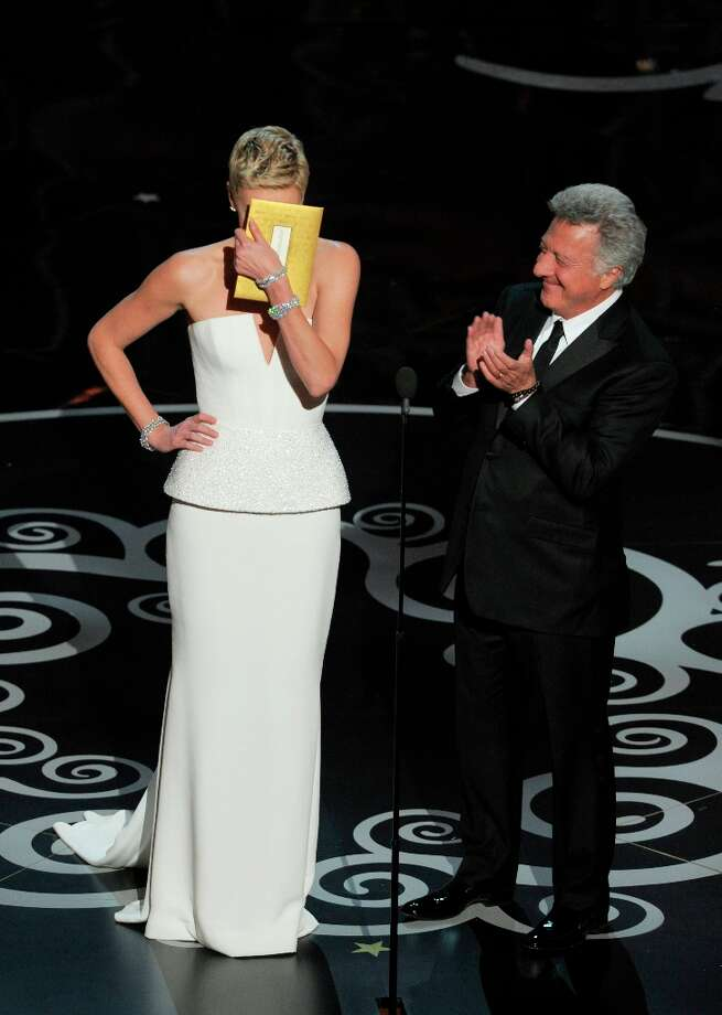 Actors Charlize Theron, left, and Dustin Hoffman present an award during the Oscars at the Dolby Theatre on Sunday Feb. 24, 2013, in Los Angeles.  Hoffman tells Theron she's a great dancer. (Photo by Chris Pizzello/Invision/AP) Photo: Chris Pizzello, Associated Press / Invision