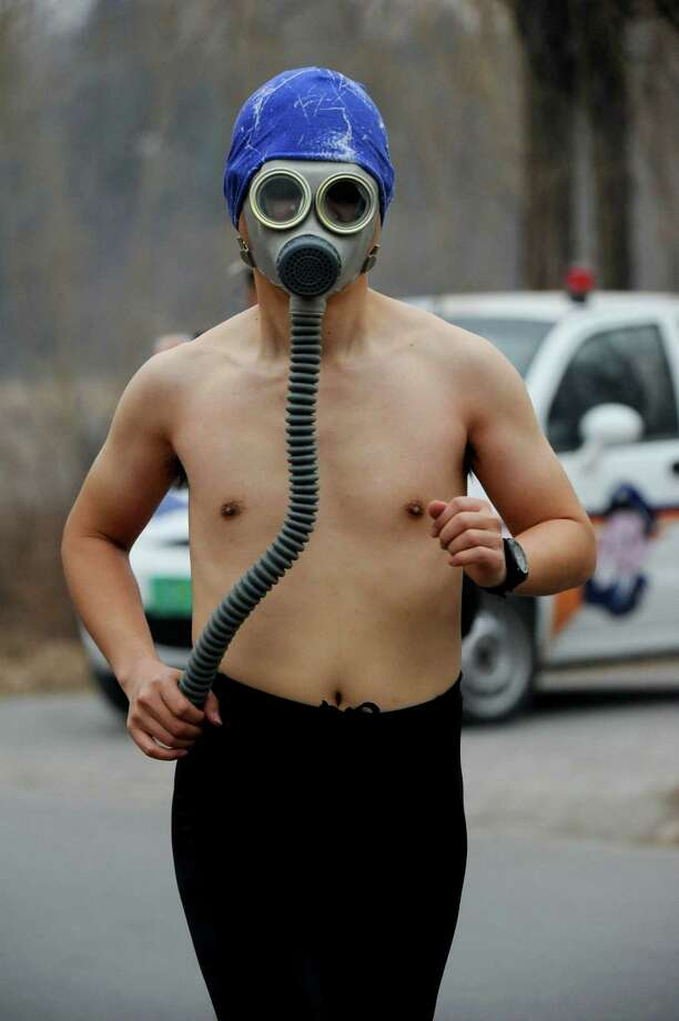 "Beijing's air - still safer to breathe than your car's exhaust:A racer protects his lungs as he bares his chest in the 3.5k Undies Run at Olympic Park in Beijing. In January, Beijing scored a 755 on the EPA's Air Quality Index, a 500-point scale in which 150 is ""unhealthy"" and above 300 is ""hazardous."" Photo: ChinaFotoPress, ChinaFotoPress Via Getty Images / 2013 ChinaFotoPress"