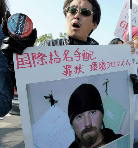 A pro-whaling activist holds a can of whale meat and a poster descriding the man pictured as an